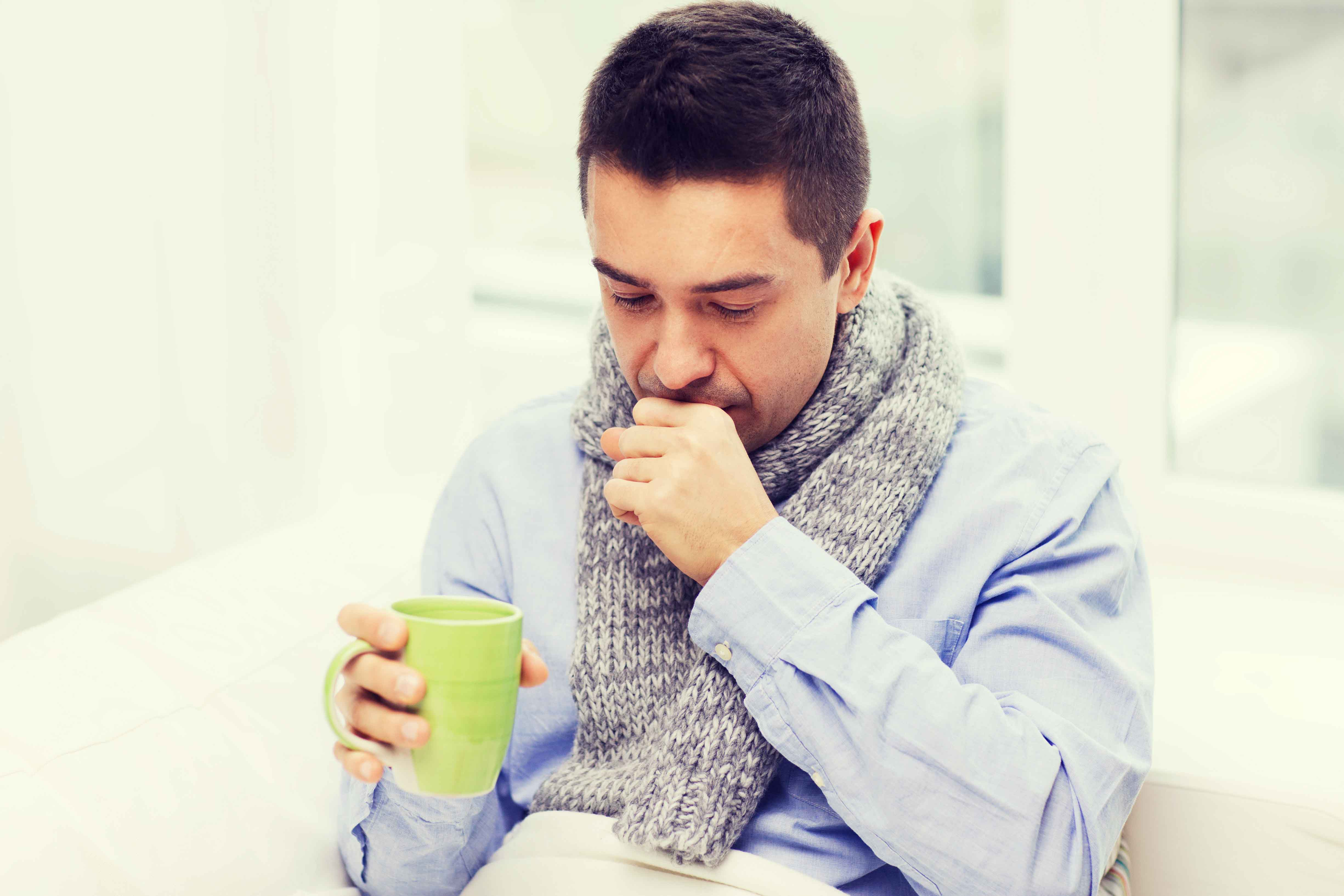man wrapped up in a scarf with a hot drink